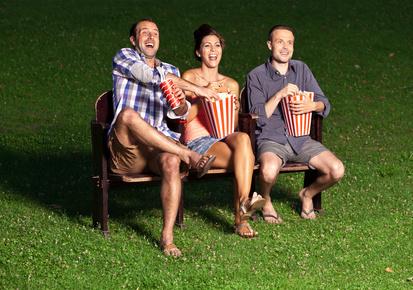 Trois amis regardant un film en plein air